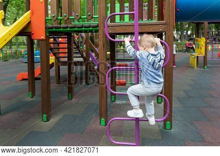 Back View Cute Adorable Caucasian Blond Little Toddler Boy Kid Having Fun Enjoy Climbing Metal Stair
