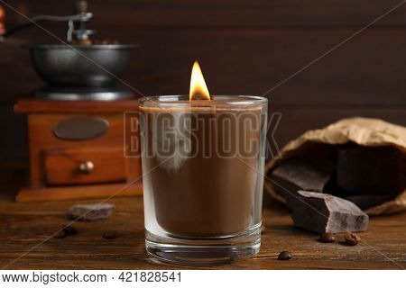 Scented Candle With Burning Wooden Wick, Coffee Beans And Chocolate On Table