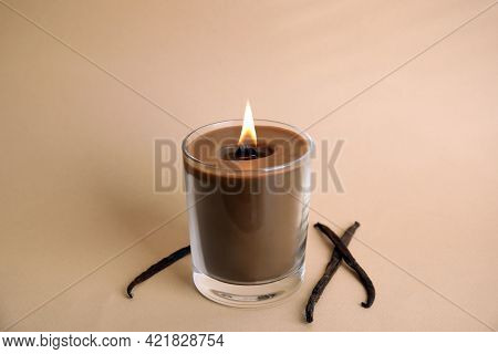 Beautiful Candle With Wooden Wick And Vanilla Sticks On Beige Background