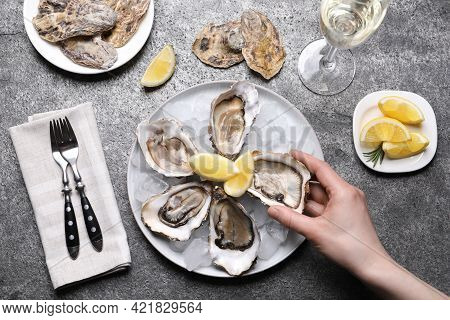 Woman Eating Tasty Fresh Oysters At Grey Table, Top View