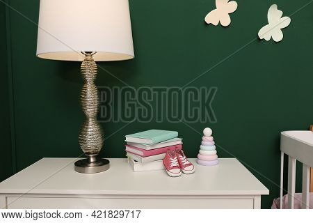 Books, Booties, Lamp And Toy Pyramid On Chest Of Drawers In Baby Room