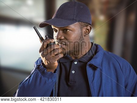 Composition of male security guard using walkie talkie over blurred background. security and safety concept digitally generated image.