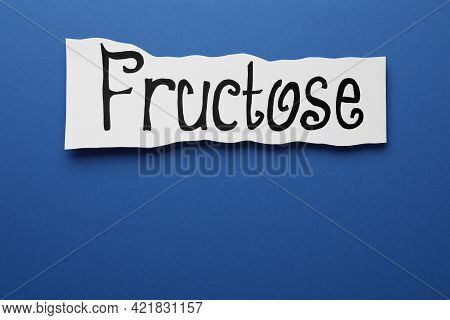 Paper Sheet With Word Fructose On Blue Background, Top View. Space For Text