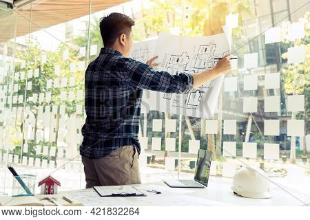 Interior Designer Or Architect Reviewing Blueprints And Holding Pencil Drawing On Desk At Home Offic