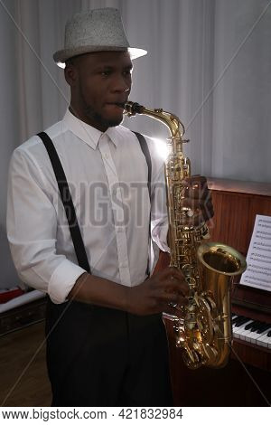 African-american Man Playing Saxophone Indoors. Talented Musician