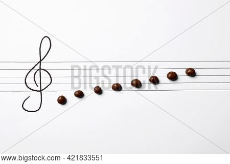 Music Staff With Treble Clef And Chocolate Candies As Notes On White Paper, Flat Lay. Creativity Con