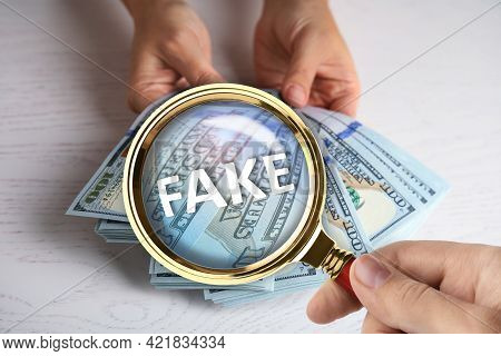 Woman With Magnifying Glass Detecting Fake Money, Closeup
