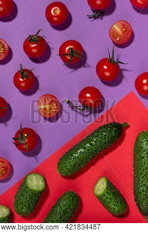 Ripe Cherry Tomato And Green Gherkin Cucumber With Shadow On Contrast Red And Purple Background, Top
