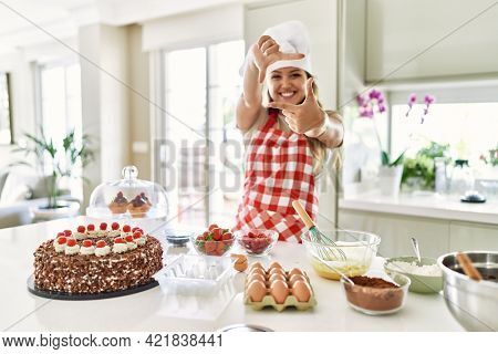 Beautiful young brunette pastry chef woman cooking pastries at the kitchen smiling making frame with hands and fingers with happy face. creativity and photography concept.