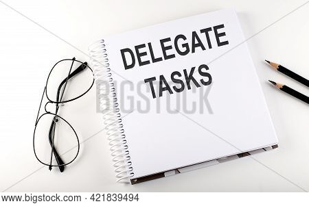 Notebook With Text Delegate Tasks On White Background
