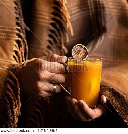 Man Holding Glass Mug Of Hot Orange Or Lemon Drink While Wrapped In Blanket. Male Hands Holding Tran
