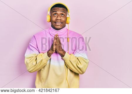 Young black man listening to music wearing headphones begging and praying with hands together with hope expression on face very emotional and worried. begging.