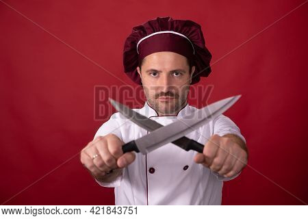 Handsome Chef In Uniform Holding Two Crossed Knifes On Red Background