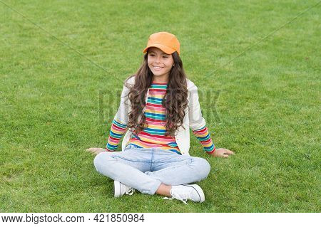 Young Kid. Happy Kid Sit On Green Grass. Female Child. Childhood And Girlhood. School Age