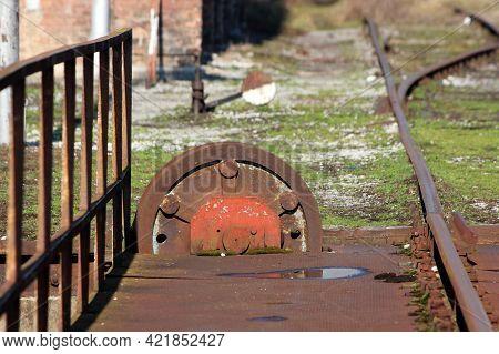 Large Vintage Rusted Old Railway Turntable Or Wheelhouse Cogwheel Mounted On Side Of Railroad Tracks