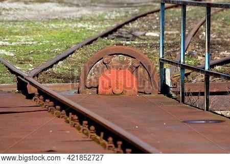 Rusted Old Railway Turntable Or Wheelhouse Cogwheel Mounted On Side Of Railroad Tracks Used For Turn