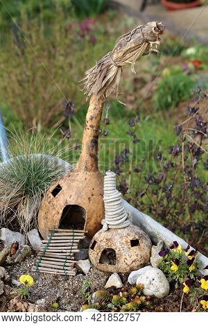 Two Small Carved Out Dry Squashes Made To Look Like Two Small Fairy Houses With Wooden Stairs Entran