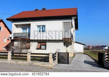 White Suburban Family House With Unusual Balcony And New Windows On First Floor Surrounded With Ston