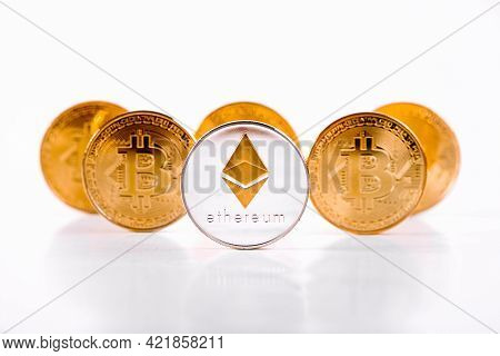Crypto Currency Ethereum Coin Standing In Front Of Golden Bitcoins On White Background. Ethereum Dom