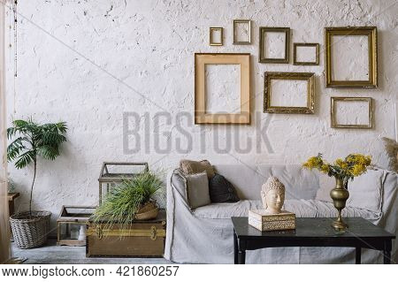 Bohemian Styled Living Room Couch Against White Concrete Wall With Empty Picture Frames, Compact Bla