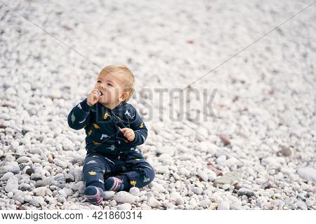Cute Baby In A Blue Overalls Sits On A Pebble Beach, Turning His Head To The Left And Holding A Pebb