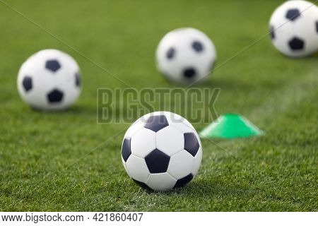 Training Classic Soccer Football Balls On Grass Field. White And Black Soccer Balls And Training Con