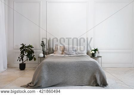Large Comfortable Bed With Grey Cover And Comfy Pillows In Spacious Stylish Modern White Bedroom In