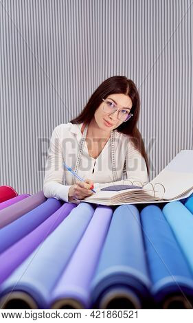 Female Stylish Drapery Store Or Warehouse Supervisor In Eyeglasses And Measure Tape Making Inventory