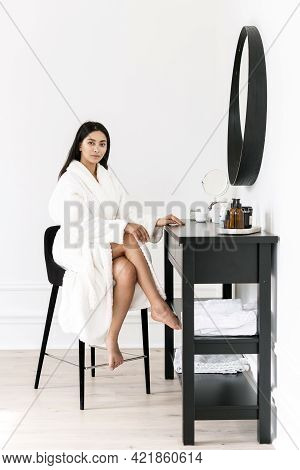 Natural Beauty And Morning Routine Concept. Vertical Shot Of Young Asian Woman In Soft Bathrobe Sitt