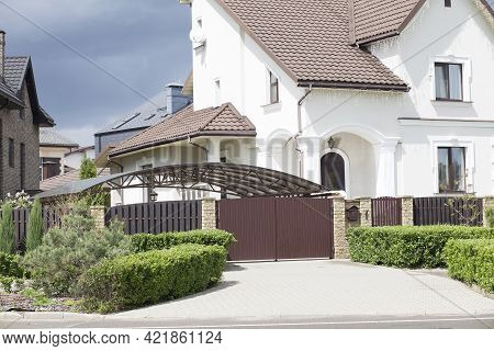 Gateway To A Private Beautiful Well-kept House. The Facade Of A White Plastered Rich Two-story House