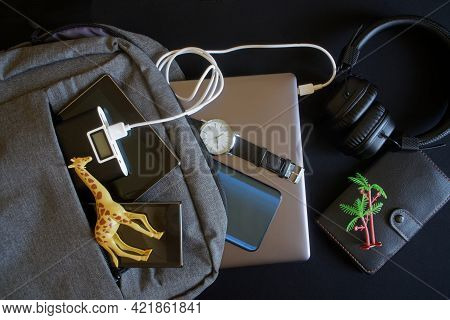 Travel Gadgets Near A Gray Textile Backpack And Souvenirs From Tropical Countries On A Dark Surface.