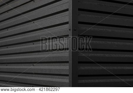 Details Of Black Corrugated Iron Sheet Used As A Facade Of A Warehouse Or Factory. Texture Of A Seam