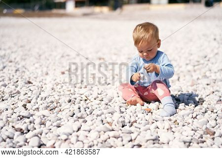 Cute Baby In A Blue Blouse And Red Pants Sits On A Pebble Beach, Bowing His Head And Holding Pebbles