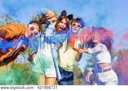 Beautiful Young Man And Woman Hold Light Up Colored Smoke Bombs - Happy Friends Having Fun In The Pa