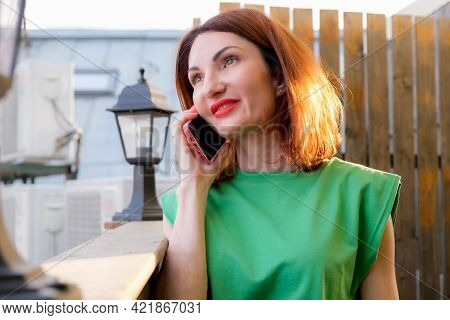 Attractive Girl With Red Hair In A Green Blouse Is Talking On A Mobile Phone On The Open Terrace Of