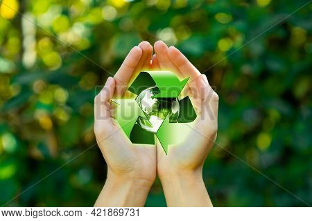 Save Planet Earth Day Concept. Female Hands With Recycle Logo Over Green Forest Nature Background. E