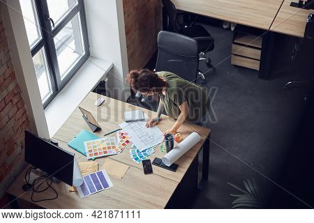 High Angle View Of Interior Designer Or Architect In Casual Wear With Messy Hairdo Working With Colo