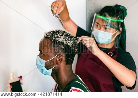 Professional Hairstylists With Masks On Their Faces, Doing A Hair Job On A Man In A Beauty Salon Dur