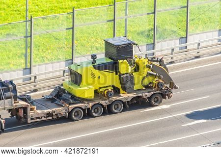 Truck With A Long Trailer Platform For Transporting Heavy Machinery, Loaded Tractor Without Wheels A