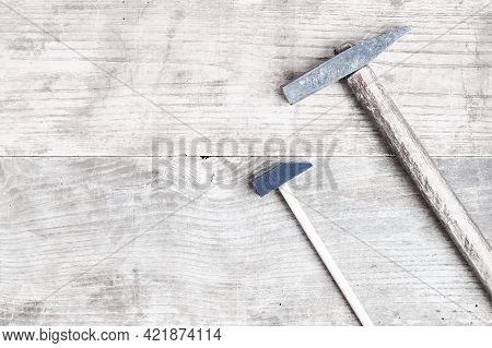 Toy And Real Hammers On Old Bleached Boards. Rustic Vintage Tools. Place For Text. Scattered Iron Na