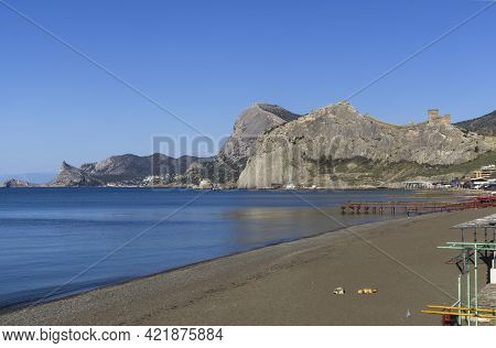 Two Dogs Lie On An Empty Sandy Beach. Sudak, The Middle Of The Sudak Bay, View Towards The Resort Vi