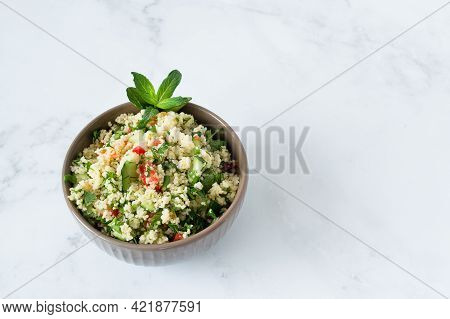 Traditional Oriental Salad Tabouleh With Couscous Or Bulgur On A White Marble Background. Ingredient