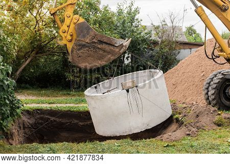 Excavator With A Bucket, Lowering Into The Pit On Steel Cables Concrete Sewer Ring. Construction Or
