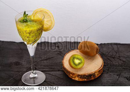 Kiwi Smoothie Garnished With Mint And Lemon In A Glass On A Black Background Near Kiwi. Horizontal P