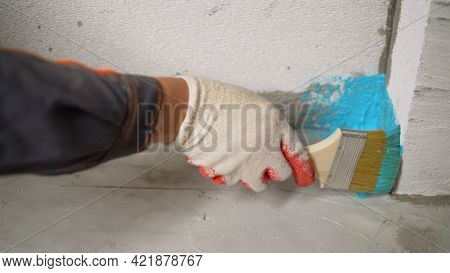 A Worker Is Applying Waterproofing Paint To The Floor In The Bathroom. The Process Of Applying Water