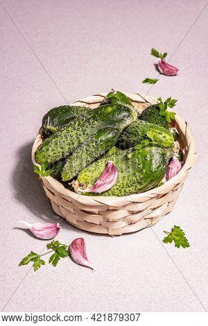 Trendy Ugly Organic Cucumbers, Garlic Cloves, Parsley Greens In A Basket