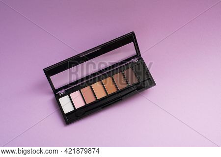 Palette Of Basic Eyeshadows On A Purple Background. Makeup Concept