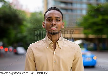 Portrait Of Handsome Black Young African Businessman Smiling Outdoors In City