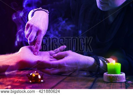 Witch Is A Fortune Teller Reading Good Luck Close-up. Fortune Teller Guides The Lines On The Client'