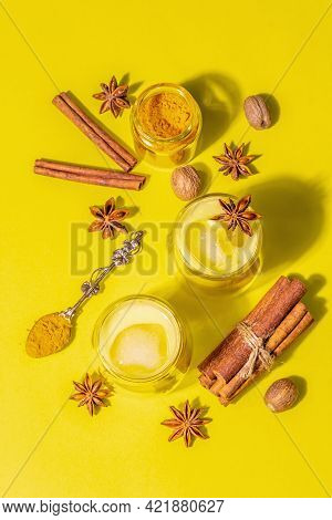 Golden Turmeric Milk With Ice On Bright Yellow Background